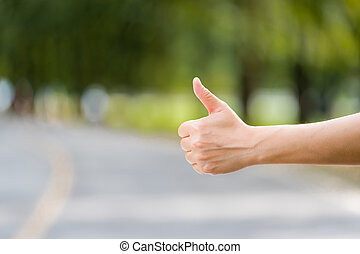 Close up woman hand hitchhiking at countryside road near...