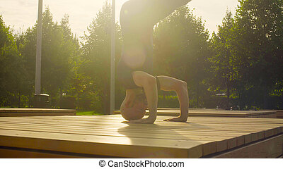 A man doing headstand in the park in summer. Shirshasana