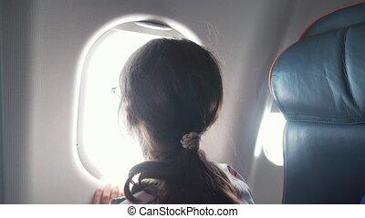 Young girl with glasses looks with interest at window of an airplane stock footage video