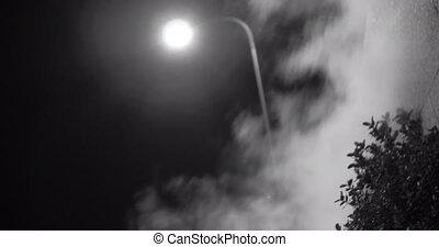 Steam against street lantern light at night, mystic black...