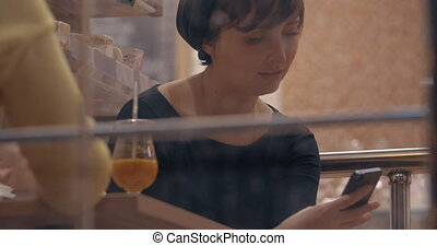 Woman communicating on cell when meeting with friend in cafe...