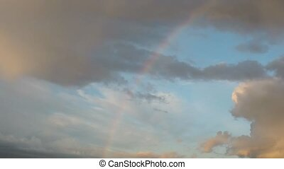 Amazing rainbow in evening sky, clouds are flying - Amazing...