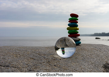Stack of dyed stones and crystal ball on the coast