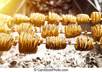 A shish kebab from yellow potatoes put on a skewer is fried...