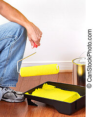 Renovation - Painter with yellow paint. Renovation