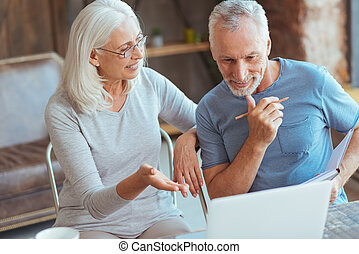 Cheerful aged couple using laptop - Have a look. Positive...