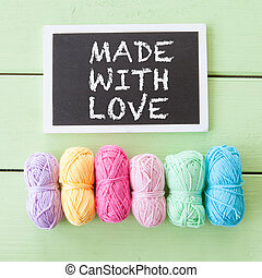 Colorful yarns for knitting - Colorful cotton yarns on green...
