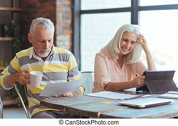 Positive aged couple sititng at the table at home - Home...