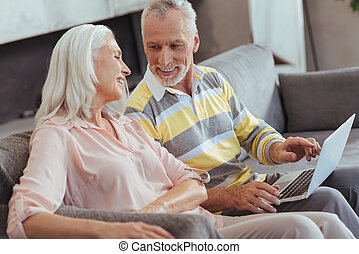 Positive loving aged couple using their laptop at home -...