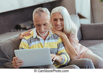 Cheerful retired couple using their laptop at home - Long...