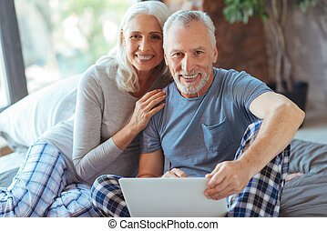Cheerful aged couple using laptop in bed - I love him....