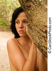 Implied nude - Naked woman hiding behind tree looking away
