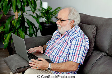 Retired man with white beard sitting in his home - Retired...