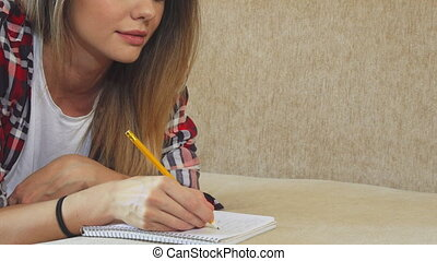 The young girl is writing in her notebook