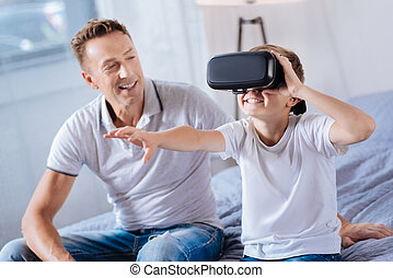 Proud father watching his happy boy test VR headset - Great...