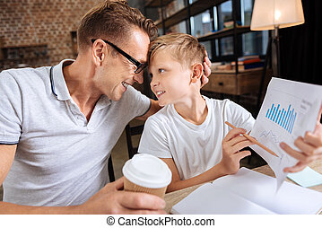 Proud father cuddling son holding printout with charts -...