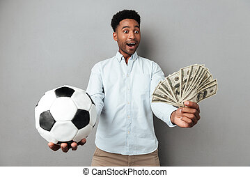 Happy smiling african man showing football and money...