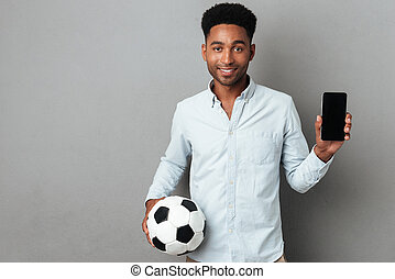 Man showing blank screen mobile phone and holding football -...