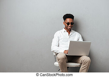 Smiling young afro american man using laptop computer while...