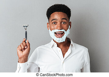 Happy cheerful african man with face in shaving foam - Close...