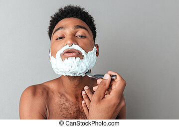 Young african man shaving with a razor