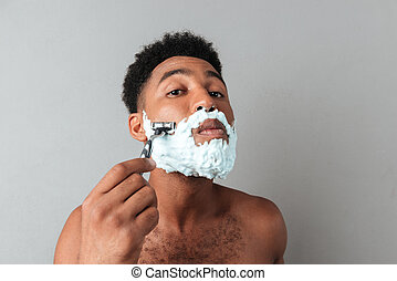 Close up of a concentrated african man shaving with a razor...