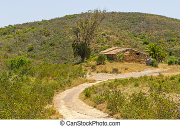 Trail and abandoned mud house in the mountain in Aljezur,...