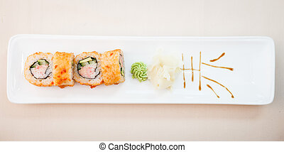 Crab maki with wasabi and ginger on a plate