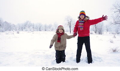 Two kids jumping together on winter landscape - Two happy...