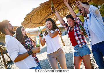 Friends partying and having fun on beach at summer - Happy...
