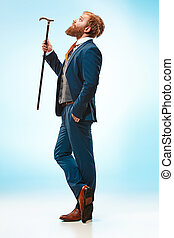 The barded man in a suit holding cane. - The bearded man in...