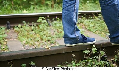 Closeup. The legs are on train tracks. The guy walking on the railroad