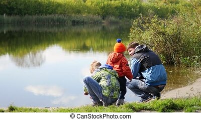 family with children resting on the shores of lake. Walks in the fresh air