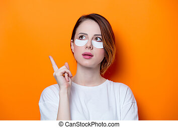 Woman using eye patch for her eyes on orange background...