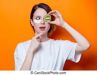 Woman using eye patch for her eyes and holding kiwi on...