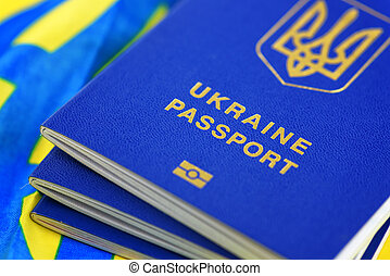 Ukrainian biometric passports on national yellow-blue flag...