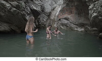 several men and women bathe in the wild mountain lake and waterfall. Travel of tourists in the mountains and rivers