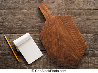 Chopping board and cookbook on wooden background with copy...