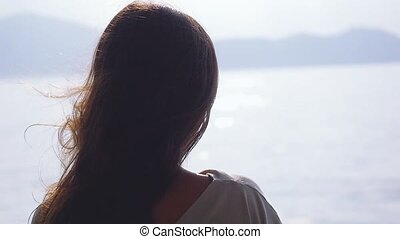 Young brunette woman standing on deck of cruise ship and...