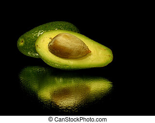 avocado on black background with water drops