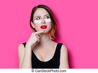 Woman using eye patch for her eyes on pink background...
