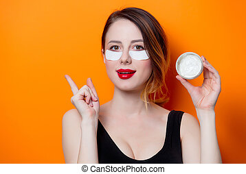 Woman using eye patch for her eyes and cream on orange...