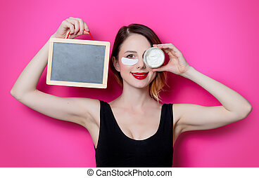 Woman using eye patch for her eyes and cream with blackboard...