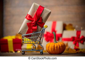 Cart full of gifts for Halloween near a little pumpkin