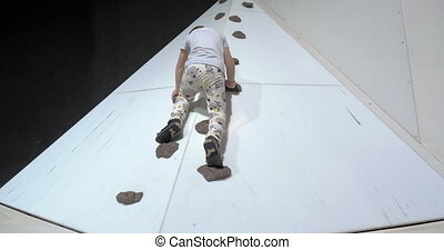 Child on rock-climbing wall - Boy getting up on the climbing...
