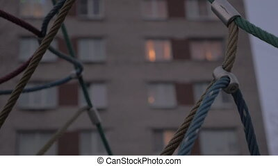 Rope web climber and house windows in the evening - Ropes of...