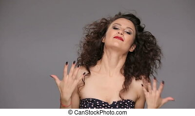 Young brunette with long brown curly hair dancing on a gray...