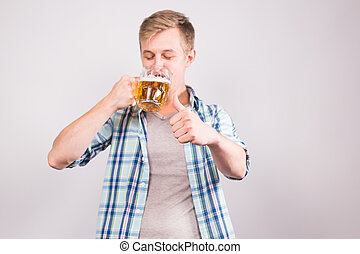 Happy young man drinking beer mug and showing thumbs up -...