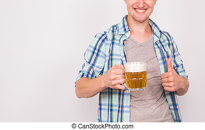 Close up of young man holding beer mug and showing thumbs up...