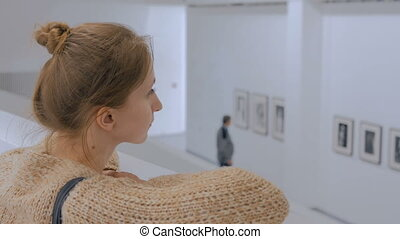 Young woman looking around in modern photo gallery....